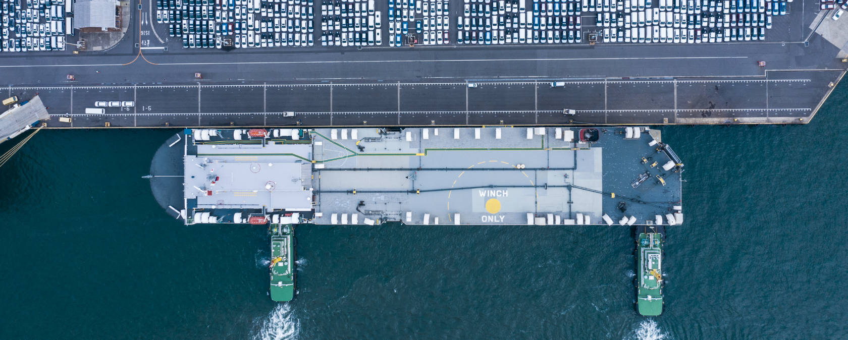 A cargo ship gets pushed into dock