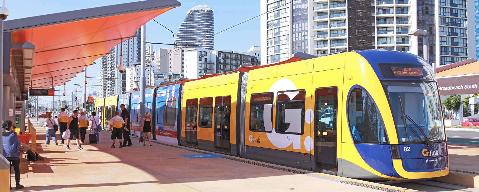 A yellow tram at a shaded tram stop