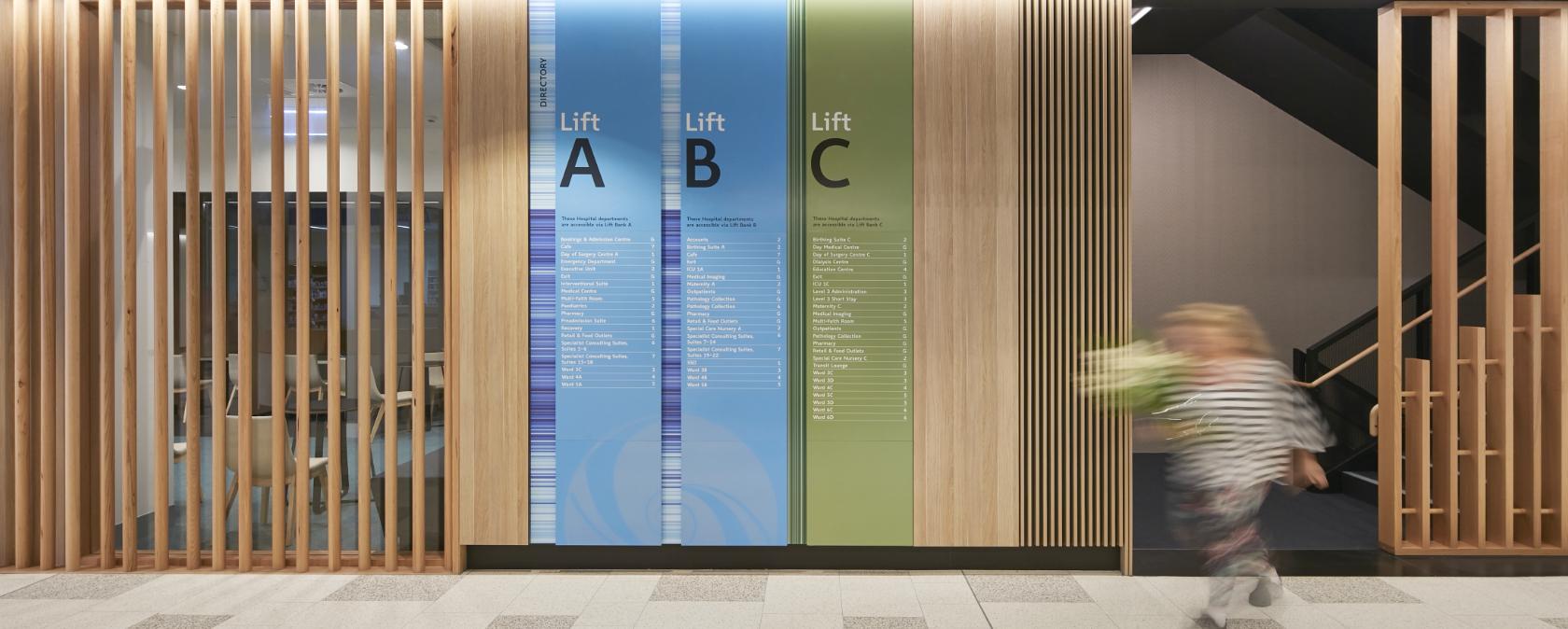A person walks quickly through a lift foyer