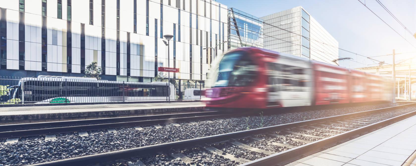 A red tram speeds down a light rail