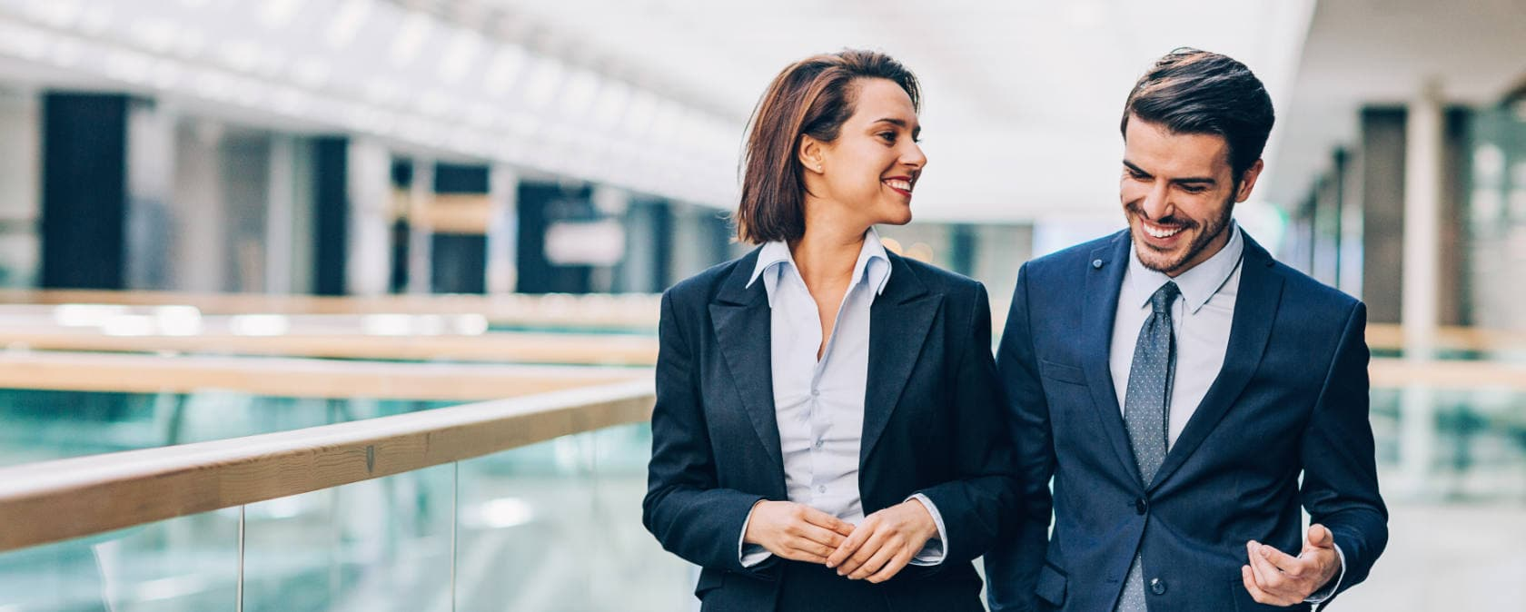 Two professionals in businesswear smile as they walk along an airy office mezzanine