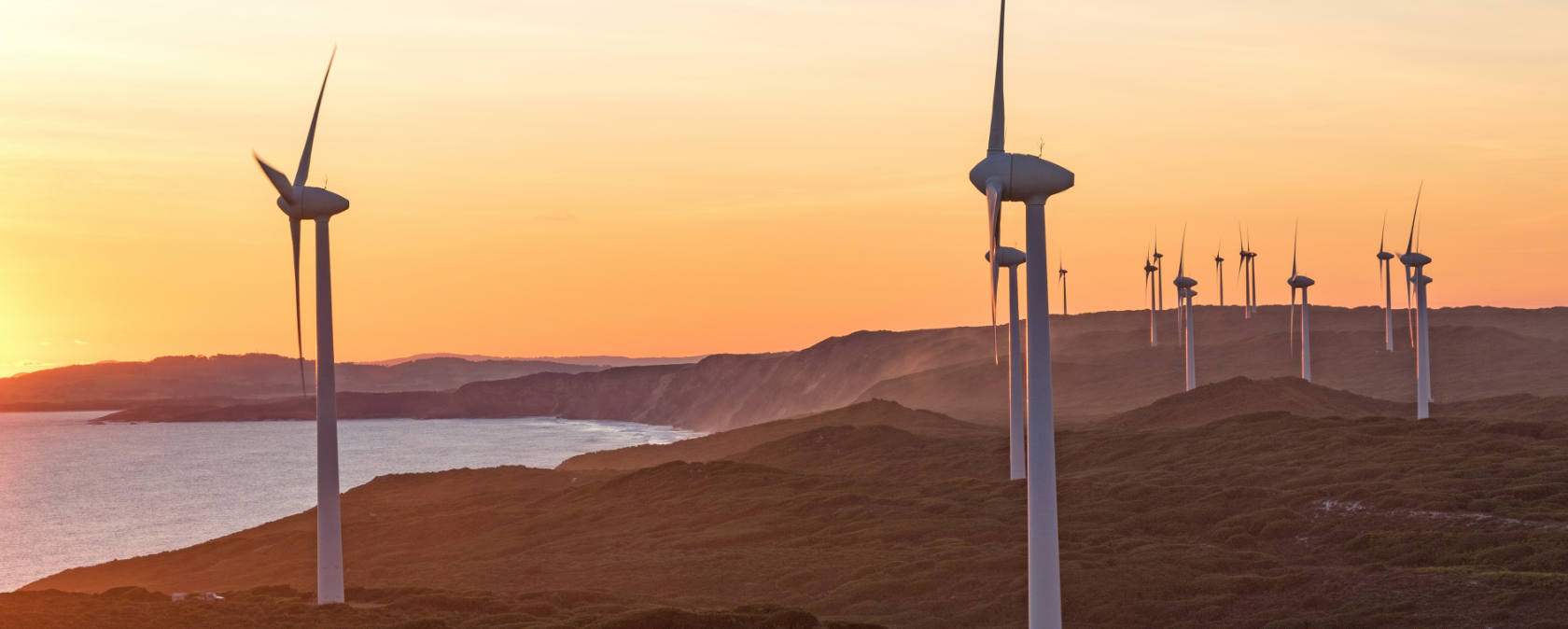 A wind farm overlooks a body of water at sunset