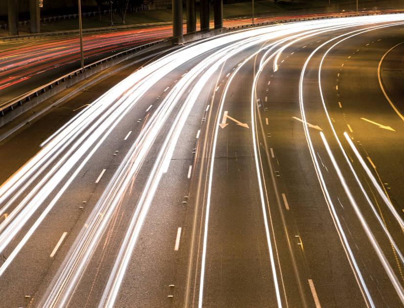 Car headlights through a night-time freeway