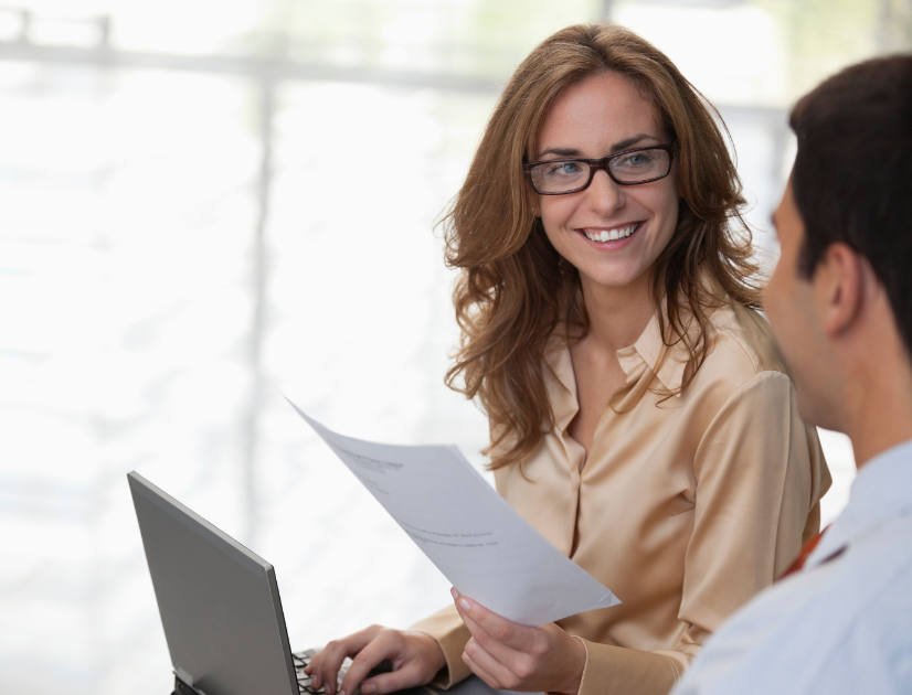A red haired woman smiles at her coworker while typing on a laptop and holding up a piece of paper