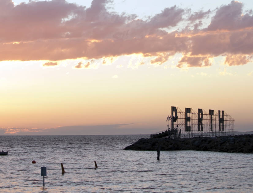 Silhouette of a cutout sign that says Perth on the shore at sunset
