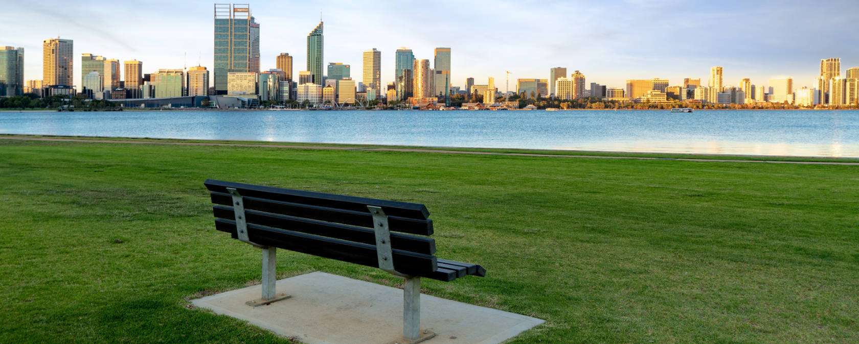 A park bench looking out at the river and Perth city horizon