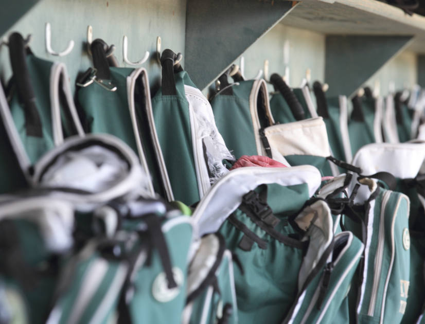 Green schoolbags hung up in a row