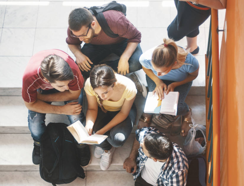 A group of students sit in a stairwell, reading a book together